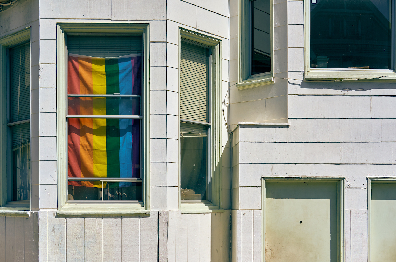 Den officiella regnbågsflaggan skymtar bakom en fönsterruta i ett amerikanskt hem med vit vägg.
