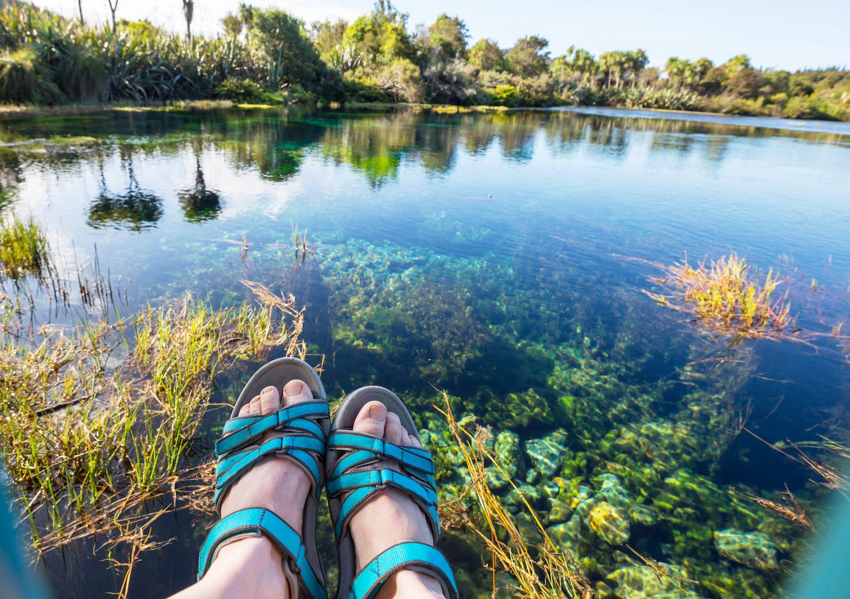 Turkosa sandaler på fötter i nedre delen av bilden. En bit bort ett vattendrag och gröna träd en fin sommardag med blå himmel.