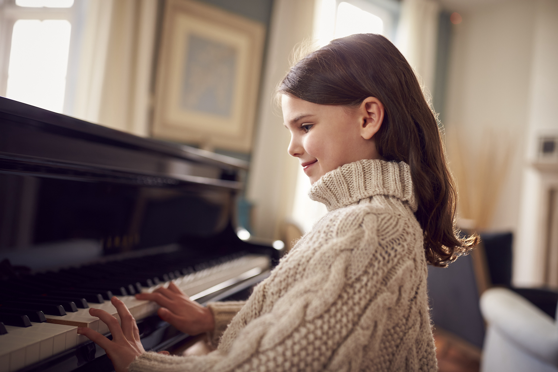 En liten flicka med långt brunt hår och stickad beige tröja intill ett piano. Hon ser glad ut. I bakgrunden syns diffus inredning i ett elegant trevligt hem.