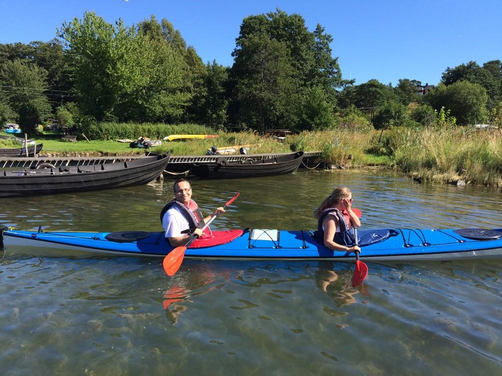 Jag paddlar en blå kajak tillsammans med en annan person i vatten med grön skog i bakgrunden.