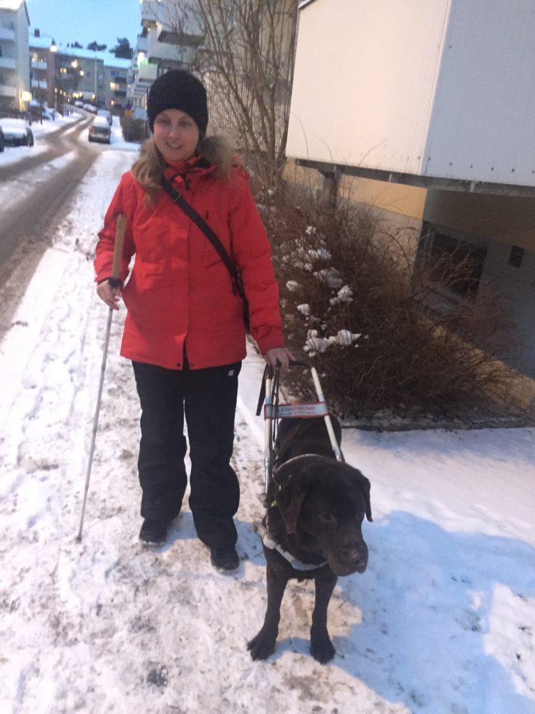 Jag står vid min ledarhund, som har brun päls, en vinterdag vid en vit husvägg. Jag har på mig svart mössa, har mörkblont långt hår. På överkropp har jag en röd jacka och svarta täckbyxor nedtill. Jag håller i hundhantaget i min vänsterhand och vit käpp i andra. I bakgrunden syns snö och lägenhetshus.