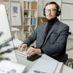 En välklädd korthårig man i mörk kostym och glasögon sitter vid skrivbord och arbetar på dator. Han är uppkopplad till telefonen med headset och ser produktiv ut. I bakgrunden syns whiteboardtavla och bokhyllor.