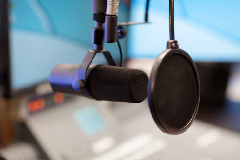 En svart mikrofon i närbild fotad i radiostudio med skärmar och mixerbord suddigt i bakgrunden.