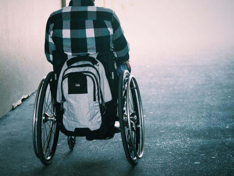 Ryggtavla av en person i rullstol. Bak på rullstolen hänger en vit ryggsäck. Personen har en vitblårutig skjorta och bakgrunden är suddig med ljus. Hela bilden har en blåaktig ton.