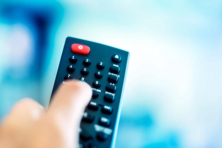 Fjärrkontroll till TV. En svart kontroll i plast med tydligt upphöjda knappar med fingrar som håller i mot en suddig bakgrund.
