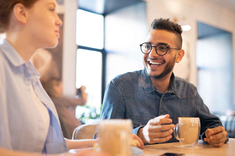En kille och tjej har ett vänligt samtal med kaffe. Killen bär svarta glasögon, har lätt färgad hud och kort hår. Han har på sig en blå jeansskjorta. Tjejen blickar en bit bort något och killen ler brett. Bakgrunden är suddig men liknar ett modernt café eller matsal.