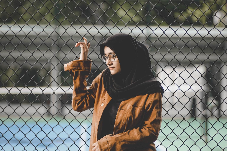 Kvinna med hijab står vid stängsel. Hennes hijab har mörk färg, hon bär glasögon och en ljusbrun jacka. Hon funderar på något och ser något bekymrad ut.