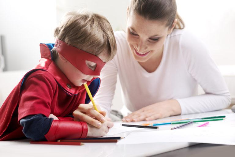 Ett barn sitter med vuxen vid bord och lär sig rita med hjälp av pennor och papper. Han har på sig en rör superhjältedräkt och mask lekfull mask som täcker runt ögonen.