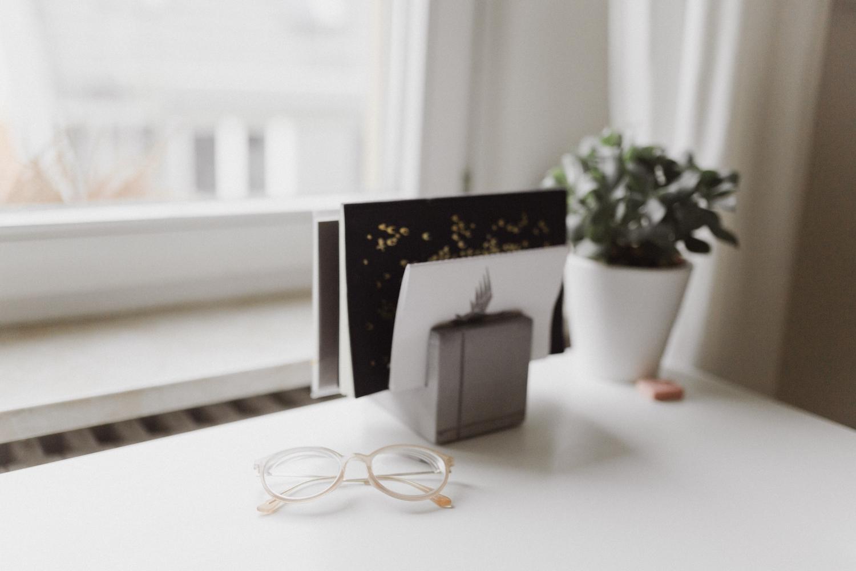 Hörnet av ett vitt bord med ett pappersställ och ihopfällda genomskinliga plastglasögonbågar samt en liten grön prydnadsväxt. I bakgrunden syns vit inredning och ett ljust fönster.