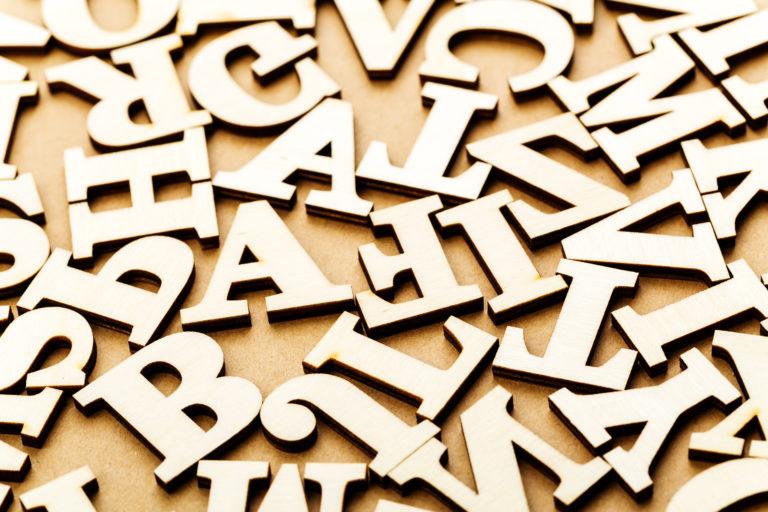 Slumpmässigt utvalda bokstäver i ljust trä ligger på ett ljusbrunt bord
