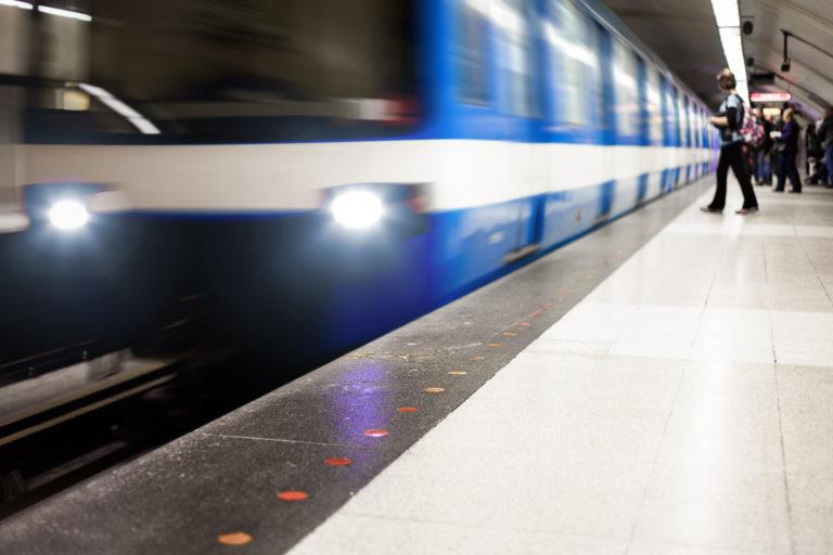 Ett blått tåg i rörelse intill perrong där människor väntar på att tåget ska stanna.