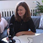 Två tjejer sitter i intervjusituation med en bordsmikrofon och dator emellan dem. De har brunt långt hår och mörka kläder. I bakgrunden syns en blå soffa och vit vägg.