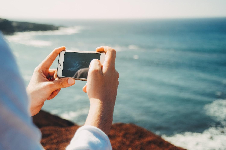 Två hände håller om en mobiltelefon och tar foto på vågorna från stranden på en resa