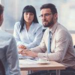 Två personer sitter vid ett bord på ett kontor och intervjuar en tredje person. De är strikt klädda i blåa och beigefärgade skjortor. I bakgrunden kan man ana något som liknar en whiteboardtavla.