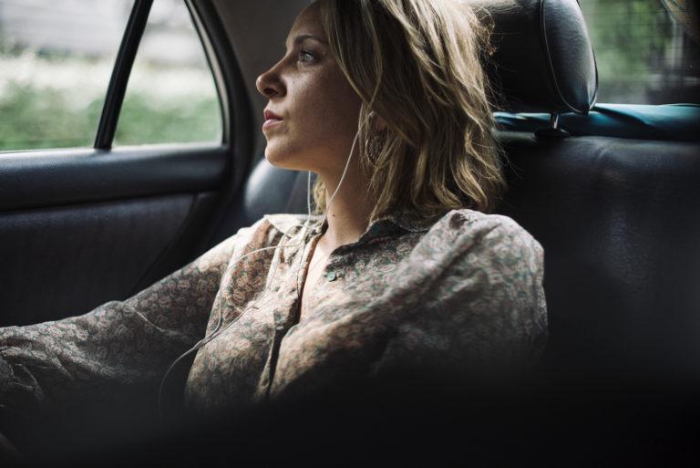 Tjej sitter i baksätet på en taxi och ser fundersam ut. Hon har blont hår och blommig beige skjorta