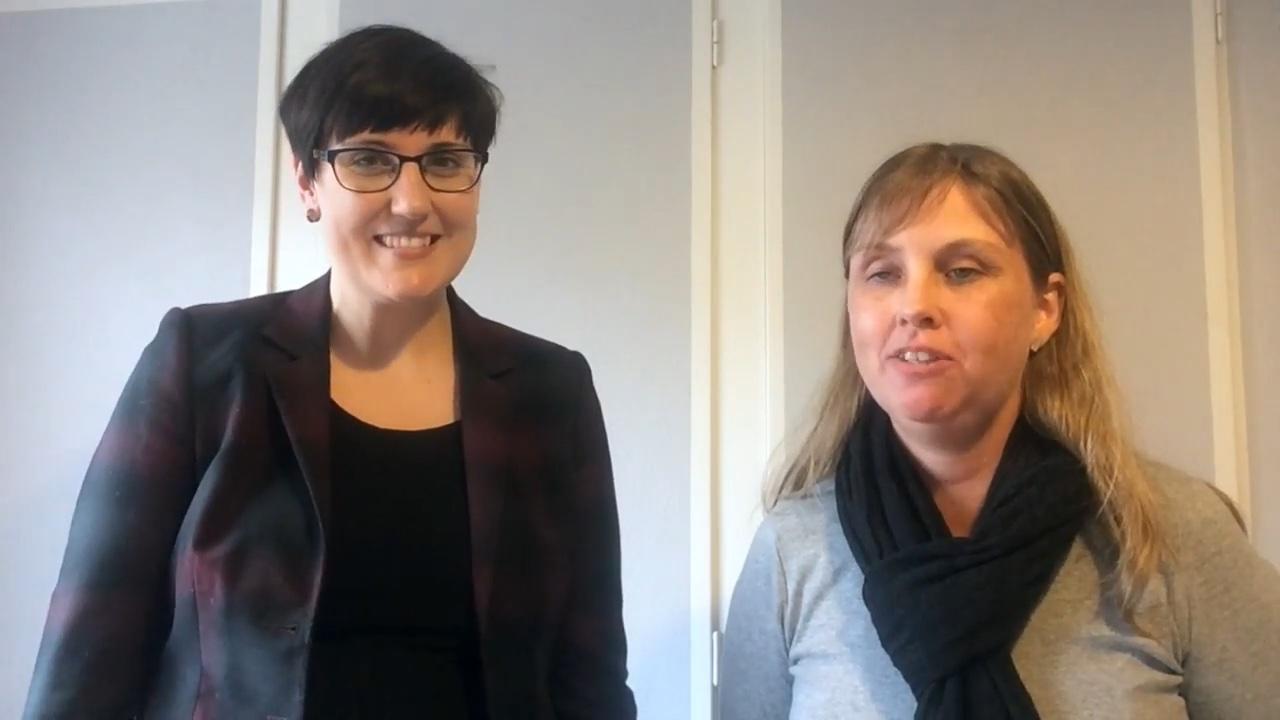 Skärmklipp från Jag och Åsa i videon där vi föreläser. Åsa har kort mörkt hår, glasögon mörk kavaj. Jag har på mig en grå tröja och svart scarf. Vi står inomhus med en gråvit vägg bakom. oss.