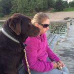 Jag och Duncan på bryggan. Jag har en rosa fleecejacka, solglasögon och håller i ett melerat koppel. Duncan, i brun päls tittar ut mot vattnet.