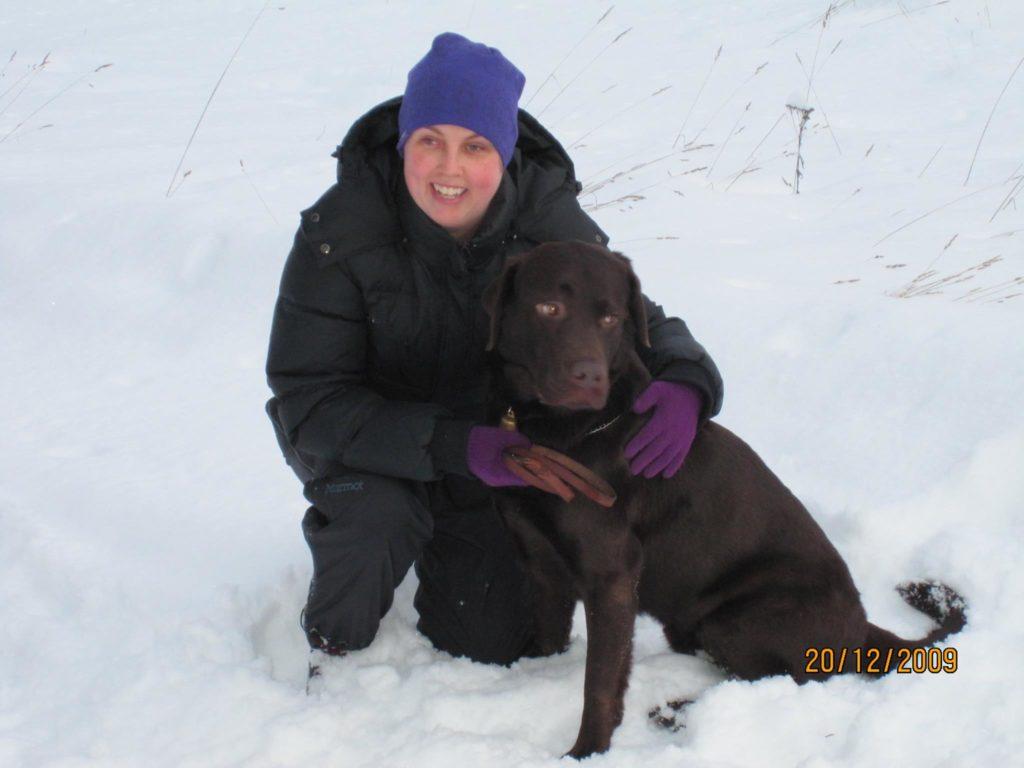 Jag och Duncan i snön. Jag står på knä och har på mig blå mössa och mörk vinterjacka. Duncan har brun mörk päls och sitter intill min famn.