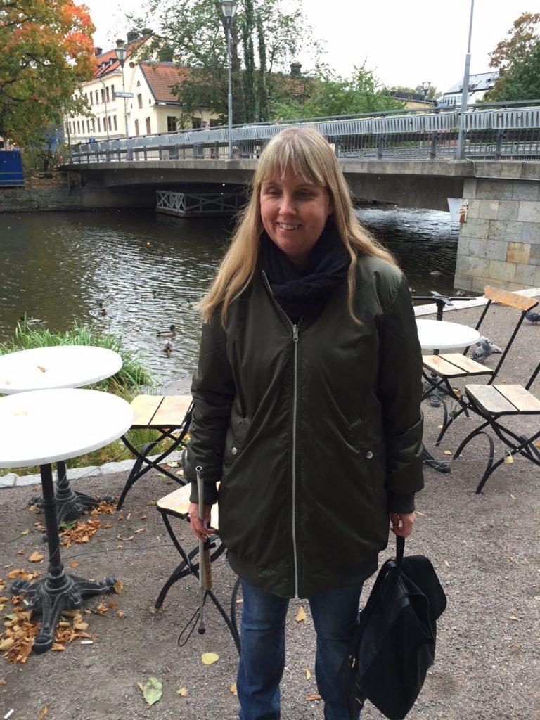 Bild på mig i lång grön bombarjacka samt jeans. Jag står framför stolar och bort på en uteservering. I bakgrunden syns en äldre bro som går över någon typ av vattendrag stadsmiljö.