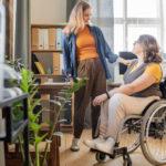 en stående tjej pratar med en tjej i rullstol