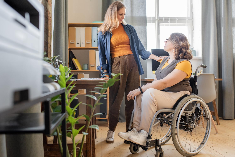 En stående tjej pratar med en tjej i rullstol. De befinner sig i ombonad kontorsmiljö. Den stående tjejen har bruna bxor, vita sneakers, orange tröja under blå skjorta samt långt blont hår. Tjejen i rullstol har byxor i beige, grå väst ovanpå orange t-shirt samt mörkblont långt hår. Den stående tjejen har sin hand på den sittandes axel.