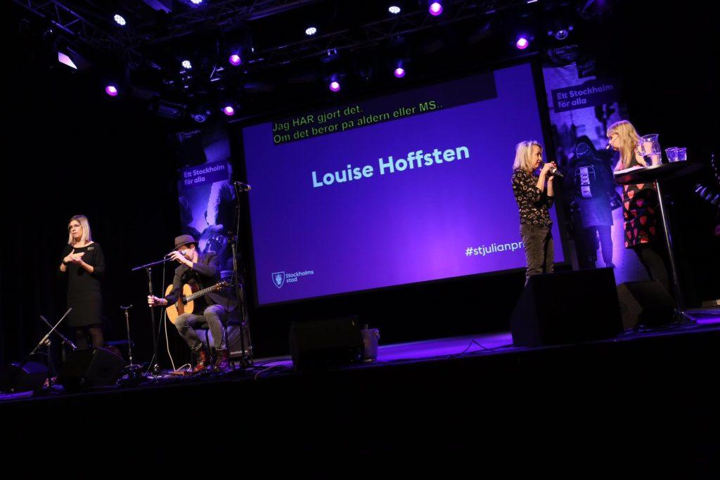 """Anna intervjuar Louise Hoffsten på S:t Julian prisutdelningen. Vi står vid ett ståbord på en scen. I bakgrunden syns en storbildsskärm med textten """"Louise Hoffsten"""". Hela scenen är belyst med lila ton. Jag har på mig svart kjol med rosa mönster. Louise har mörk tröja och byxor."""