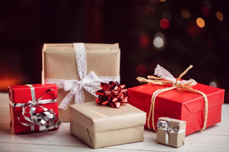 Inslagna julklappspaket i rött och beige färg mot mörk bakgrund.