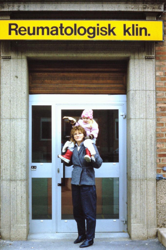 Nina utanför Avdelning 50 1985. Hon sitter på axlarna på en stående kvinna. iklädd ljusrosa mössa, jacka och vita byxor. Kvinnan har mörka ytterkläder och brunt hår.