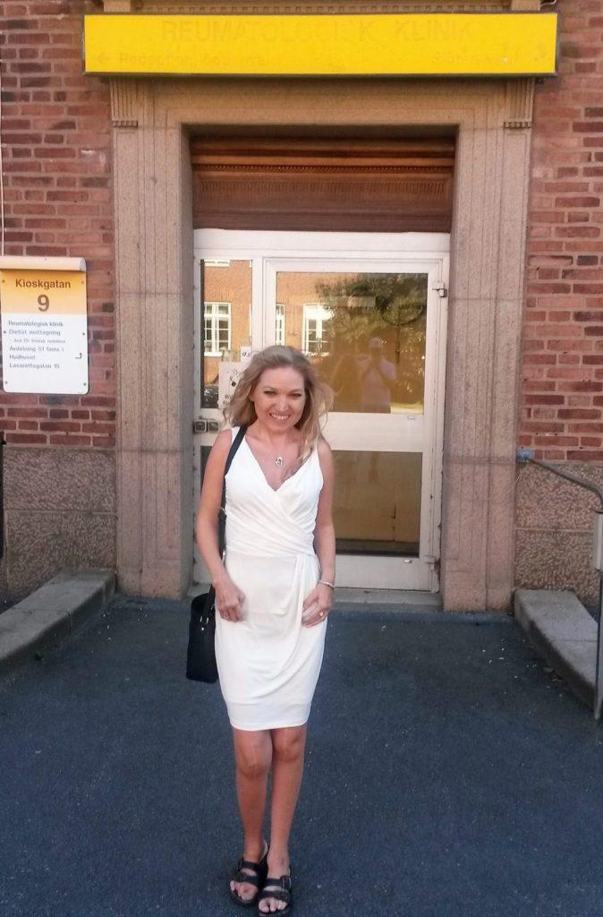 Nina 2015. Hon står utanför samma entré som bilden innan men är nu äldre, med långt blont hår, bär vit kjol och svarta sandaler.