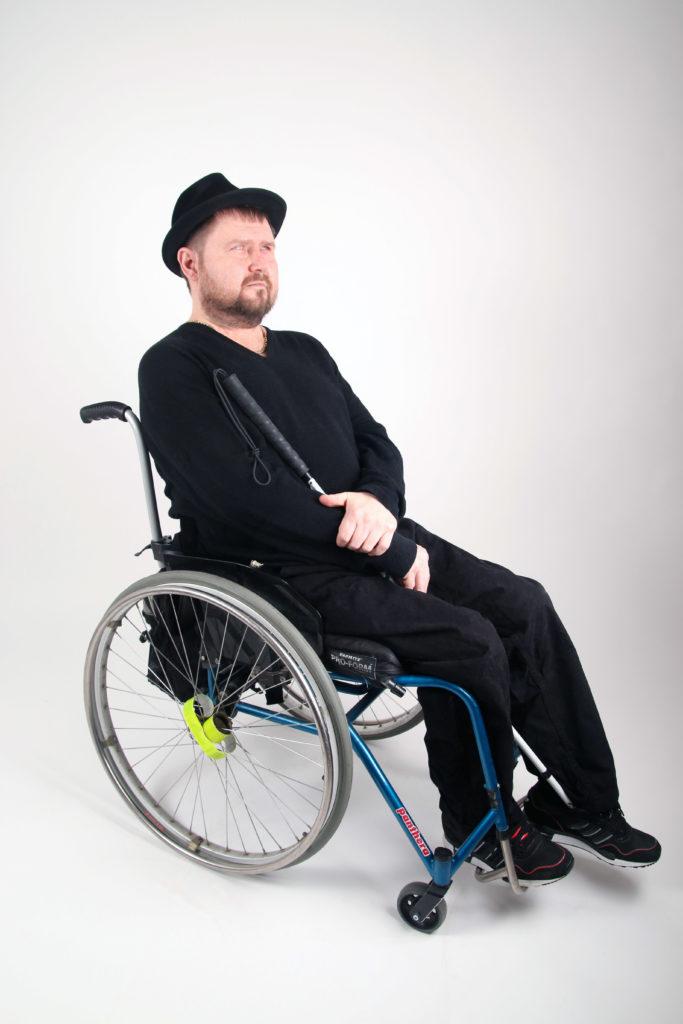 Petri Mykkenän sitter i rullstol i fotostudio med vit bakgrund. Han har på sig mörka kläder och en svart hatt. Han har kort skägg och en käpp i handen.
