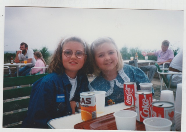 Bild på Jag och Ida. vi är barn på bilden och sitter vid ett bord bland på en uteservering intill läskedrycksburkar. Vi har på oss blåa kläder och hårspännen.