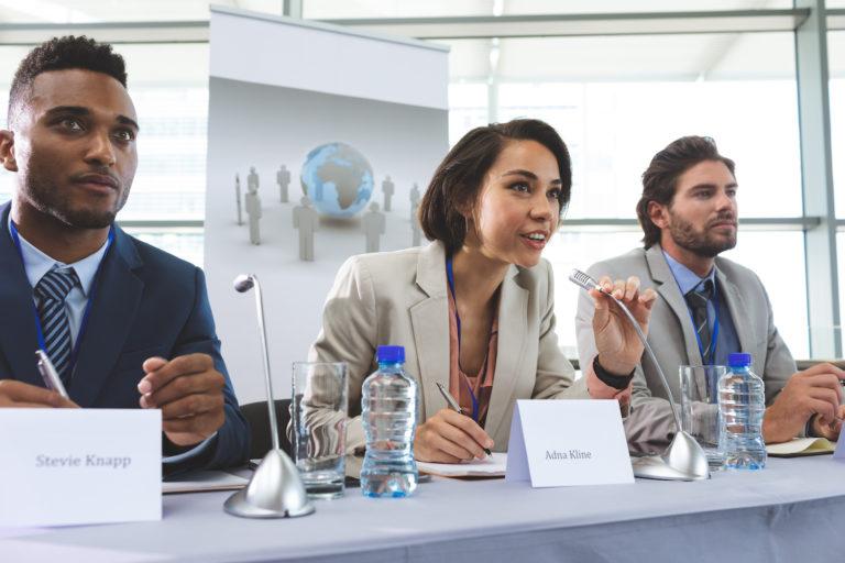 Paneldiskussion inför publik. Tre personer sitter vid ett bord. En kvinna i mitten talar i mikrofon intill två män med tydliga namnskyltar framför.