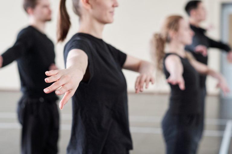 Fyra svartklädda personer tränar koreografi inför dansuppvisning