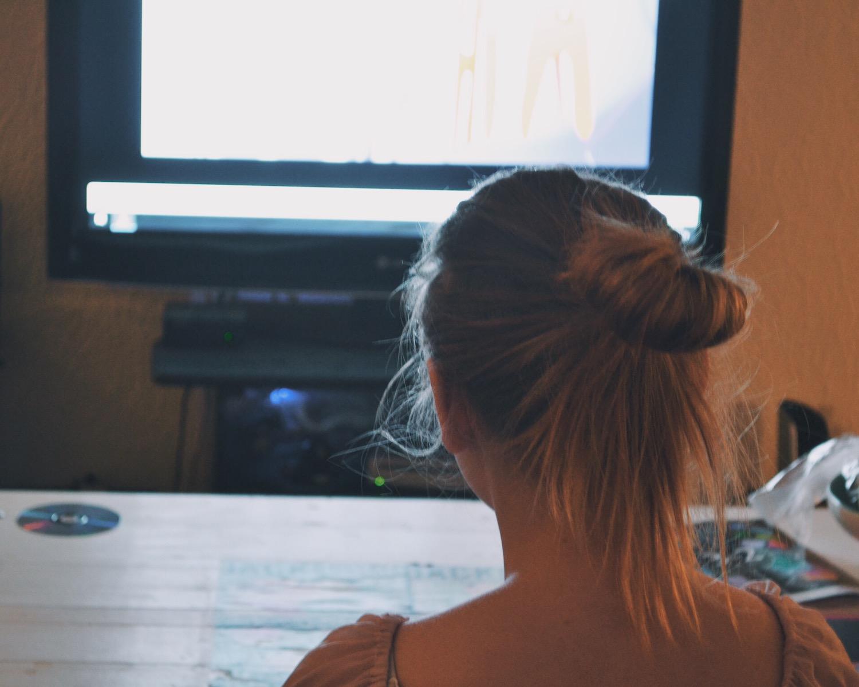 En tjej i ljust långt hår fotad bakifrån, tittar mot en tv-bild