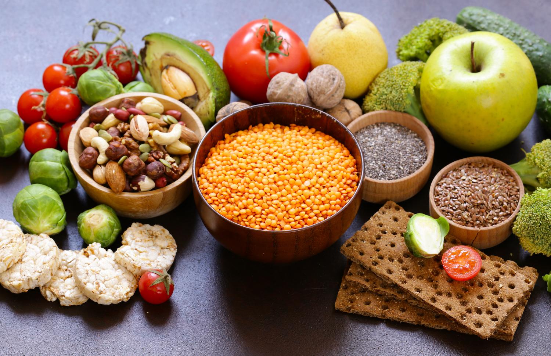 Urval av vegetarisk mat. Nötter, frön, frukt och grönsaker presenterade snyggt på ett mörkt bord