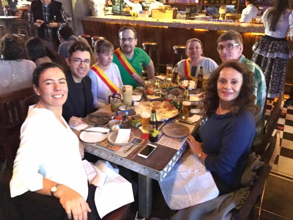 Jag sitter vid ett matbord med sex personer. i en restaurang med brun träinredning. Några av oss har band rund överkropp i gult och rött.
