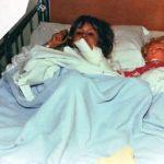 Jag som barn på sjukhuset. Jag ligger i en barnsäng intill en docka. Vi ligger båda under ett ljusblått täcke. Jag har mörkblont hår och dockan blont hår.
