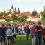Människor minglar i Almedalen en sommardag med huskroppar bakom grönska.