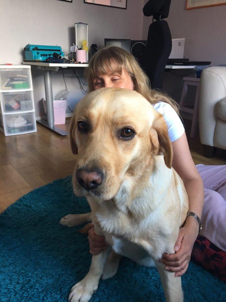 Foto på min nya ledarhund Chanti. Vi sitter inomhus på golvet, Chanti tittar in i kameran och jag sitter bakom. I bakgrunden syns mitt skrivbord.