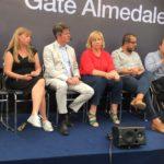 Foto på mig i panelen på Universell Design. Jag sitter bland de andra paneldeltagarna i klädd en svart kjol och vita sneakers