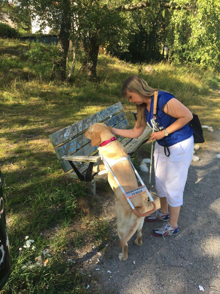 Foto på min nya arbetskamrat när hon visar mig bänken utomhus. I bakgrunden syns en skog
