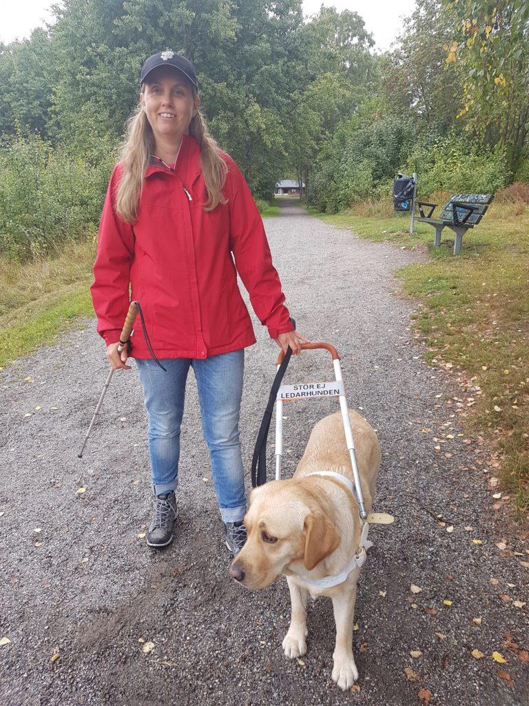 Jag och Chanti på en grusgång utomhus. Jag har på mig en röd jacka och mörk keps samt blå jeans. Hon har hunden, en ljus labrador i ett hårt sele med fast handtag i vit färg. I bakgrunden syns gröna träd och en parkbänk.