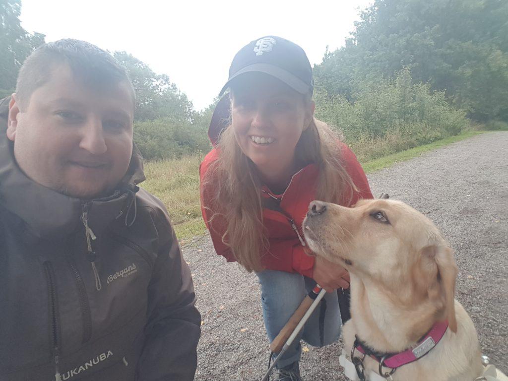 Jag, Chanti och Artem. Artem har kort mörkt hår och en gröngrå jacka. Jag har en röd jacka och mörk keps. Hunden är en ljus labrador som tittar upp mot Artem.