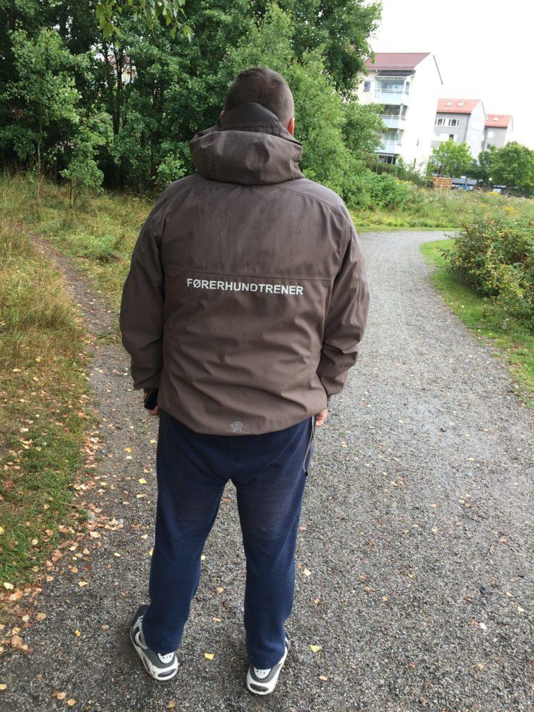 """Ledarhundsinstruktören Artem i sin jacka med text på ryggen där det står """"Förerhundtränare"""". I bakgrunden syns en grusväg, gröna träd och vita hus med lägenheter."""