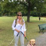Foto på mig och Chanti promenerandes på Djurgården. Jag har på mig vit skjorta, glasögon och ljusgrå byxor och skor. Chanti är en ljus labrador som bär ett svart koppel. I bakgrunden syns en grön park en somrig dag.