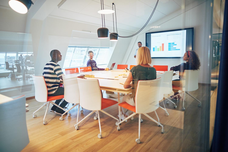 En arbetsgrupp med olika kön och olika etnisk bakgrund samtalar på kontor. samlat kring ett mötesbord. En person står och visar grafer på en storbildsskärm.