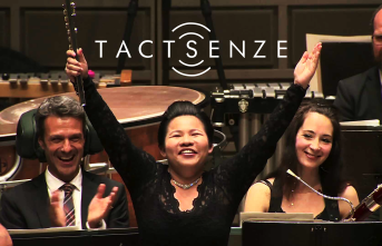 Tactsenze logo och Wu Jing. Tre personer syns i bild, en man till vänster applåderar, en tjej i mitten sträcker glatt upp händer i luften och en tjej till höger ser glad ut. De är alla finklädda i mörka tyger.