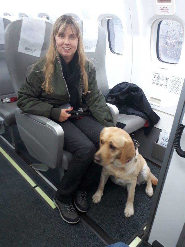 Jag sitter längst fram i flyget med Chanti. Jag har grön jacka och svarta byxor, min ledarhund är en ljus labrador.
