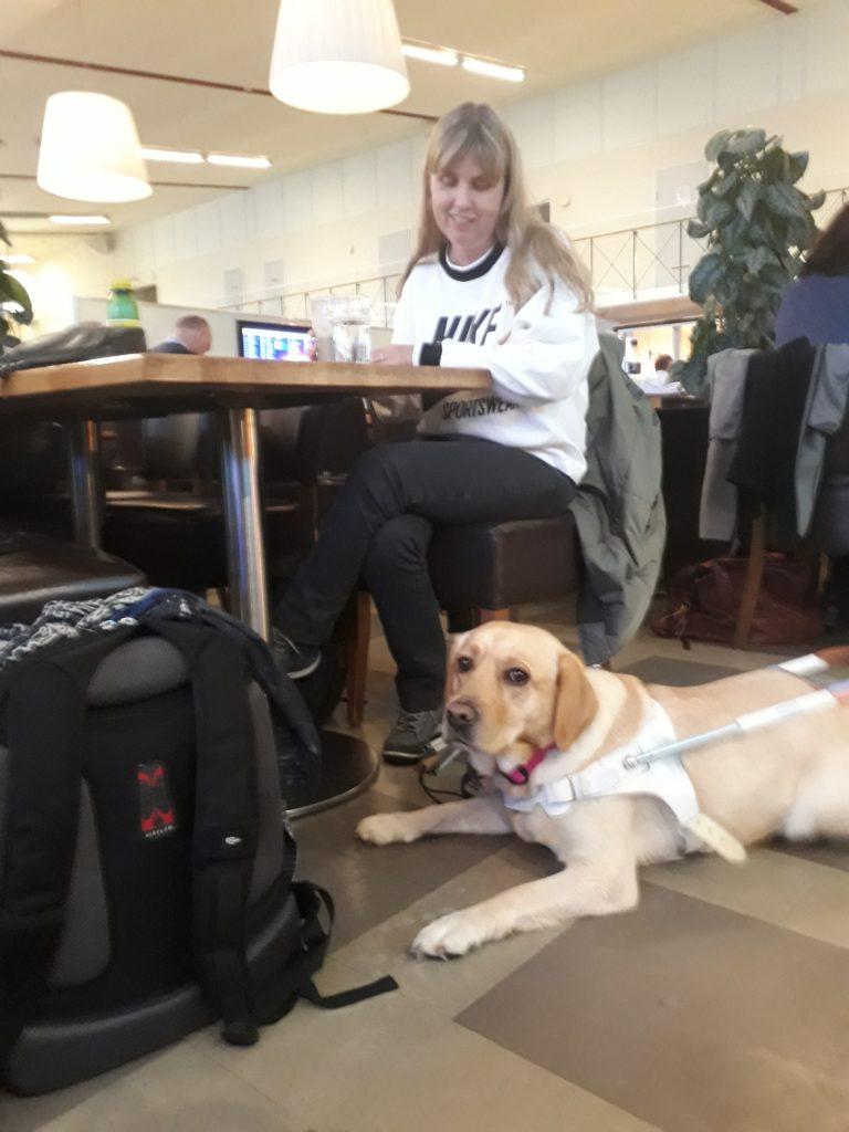 Jag sitter vid ett bord och väntar med Chanti. Jag har vit tröja och svarta byxor, min ledarhund är en ljus labrador.