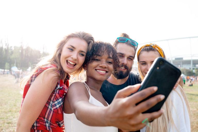 Ett kompisgäng på fyra personer tar ett gruppfot till sociala medier utomhus på en strand. Gruppen består av tre tjejer och en kille med varierande etnisk bakgrund.